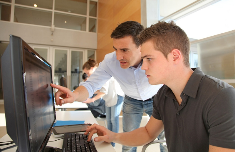 professor pointing to monitor helping a student with issue